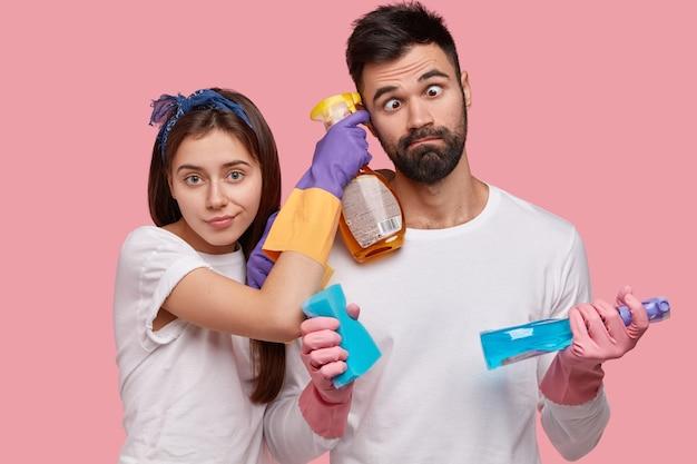 Uomo divertente con la barba lunga incrocia gli occhi, aiuta la moglie a pulire la casa, lavora insieme, fa le faccende domestiche, usa detergenti, spugna
