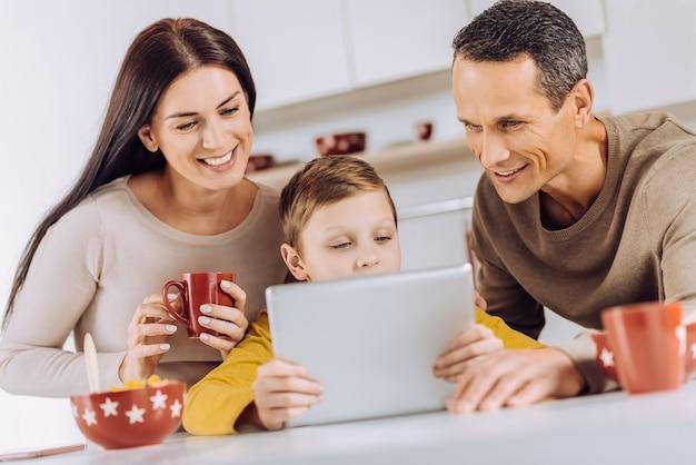 面白いビデオ。彼らの小さな太陽の近くに立って、女性がコーヒーを飲んでいる間、彼と一緒にタブレットでビデオを見ている明るい若い両親