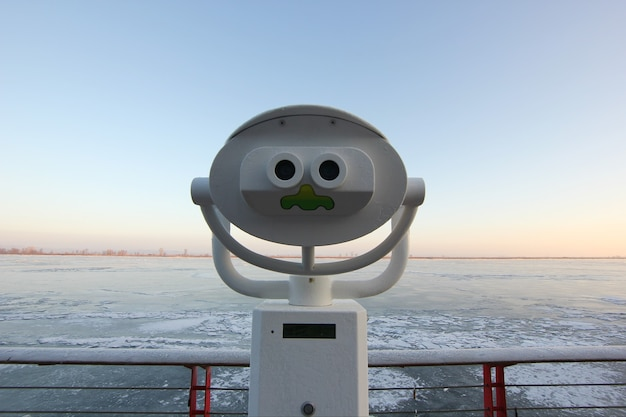 Funny view of the panoramic binoculars on the background of the frozen river