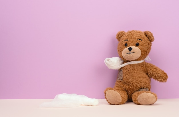 Funny vintage brown curly teddy bear with rewound paw with white gauze bandage, concept of injuries in children or animals