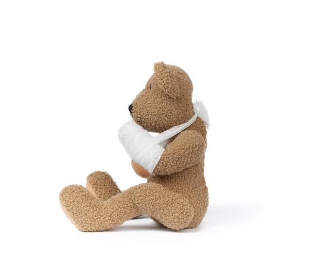 Забавный винтажный коричневый кудрявый плюшевый мишка с перемотанной лапой и белой марлевой повязкой