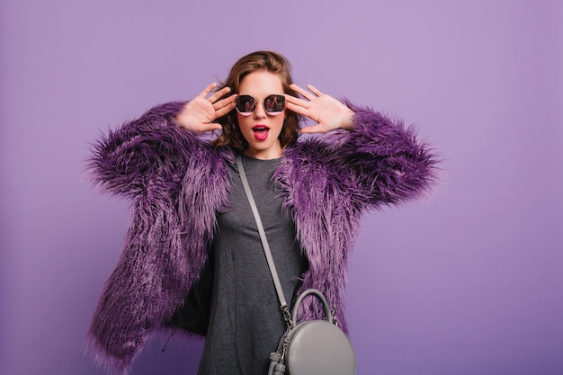Funny white girl wears elegant sunglasses making faces on purple background