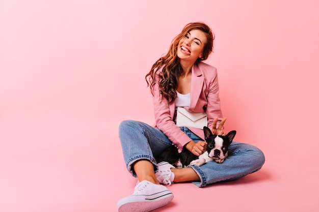Funny white girl with french bulldog making faces. indoor portrait of blithesome caucasian woman sitting on the floor with puppy.