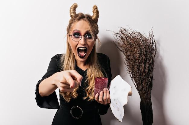웃 고 안경에 재미있는 흰색 마녀. 할로윈에서 포즈를 취하는 착한 뱀파이어.