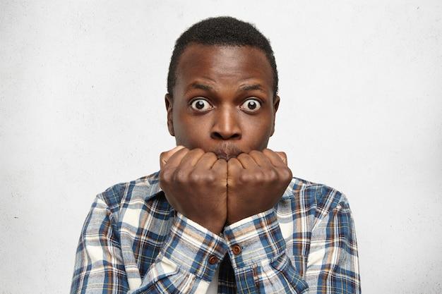 クレイジーな顔をして怖がっている市松模様のシャツを着た面白い目が広い若いアフリカ系アメリカ人の男