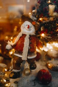面白い冬のおもちゃの雪だるまとお祝いの店先に金色のライトとクリスマスツリーの枝
