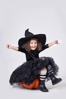 Смешная ведьма девушка в шляпе, сидя на тыкве.