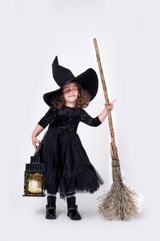 ランタンとほうきで帽子をかぶった面白い魔女の女の子