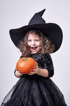 彼女の手にカボチャを持つ帽子の面白い魔女の女の子。