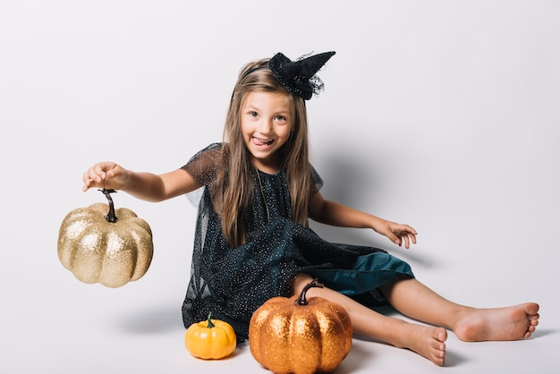 Funny witch playing with pumpkins