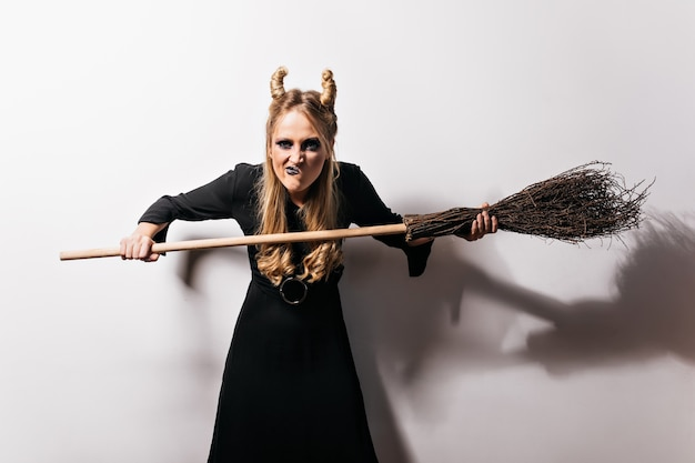 Funny witch with blonde hair standing on white wall. joyful vampire posing with broom in halloween.