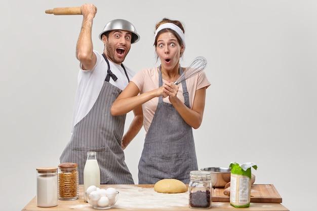 キッチンで愚かな料理人の制服を着た面白い女性と男性のレストランのシェフは、泡立て器とめん棒を持って、訪問者が料理のスキルを向上させるためにおいしい食事を準備します。カップルは料理で競います。