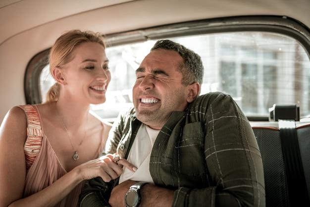 재미있는 여자. 차 뒷좌석에 앉아 웃고 있는 남편을 간지럽히며 즐거운 시간을 보내는 아름다운 여성.