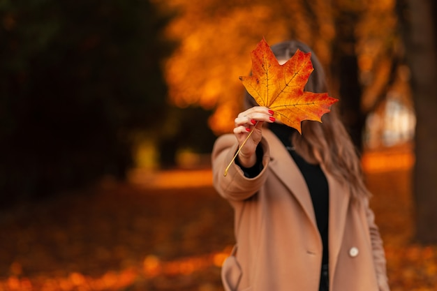 Funny woman in a beige fashionable coat shows a yellow colored autumn leaf and walks in the golden park outdoors. fall foliage close up.