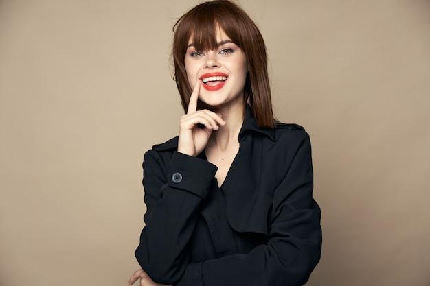 ベージュの背景の空きスペースで笑っている面白い女性の黒いコートの魅力的な笑顔