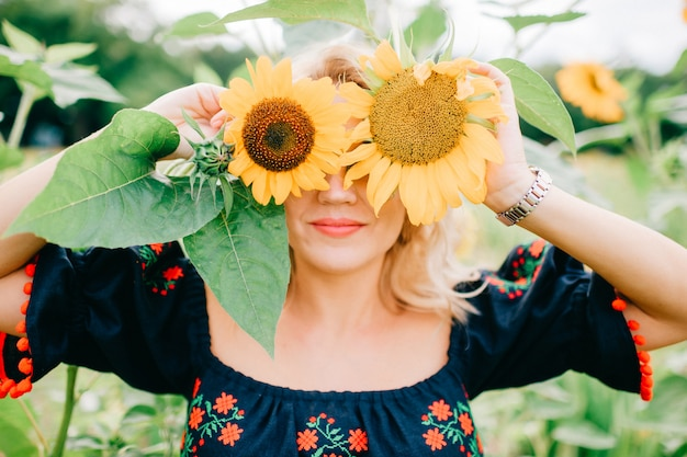 Funny woman in black dress hiding behind sunflowers