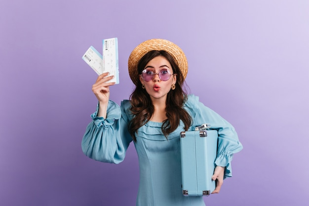 Funny woman in boater and lilac glasses stares in amazement, showing her plane tickets and blue retro suitcase.
