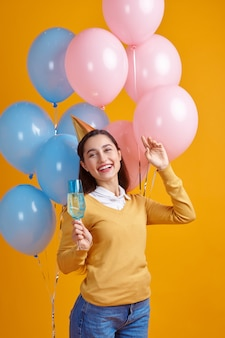 Funny woman in cap holding a glass of beverage, yellow background. pretty female person got a surprise, event or birthday celebration, balloons decoration