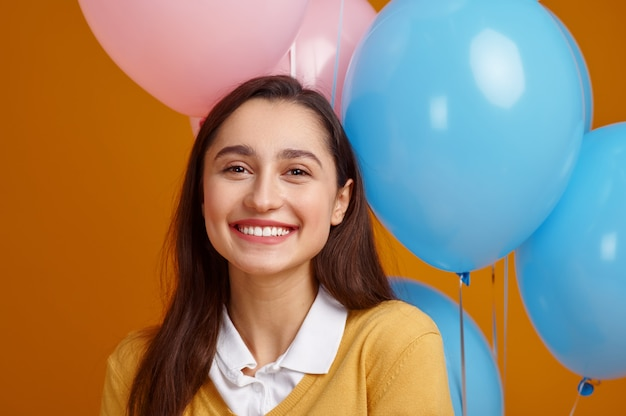 Funny woman in cap. pretty female person got a surprise, event or birthday celebration, balloons decoration