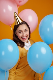 Funny woman in cap, yellow background. pretty female person got a surprise, event or birthday celebration, balloons decoration
