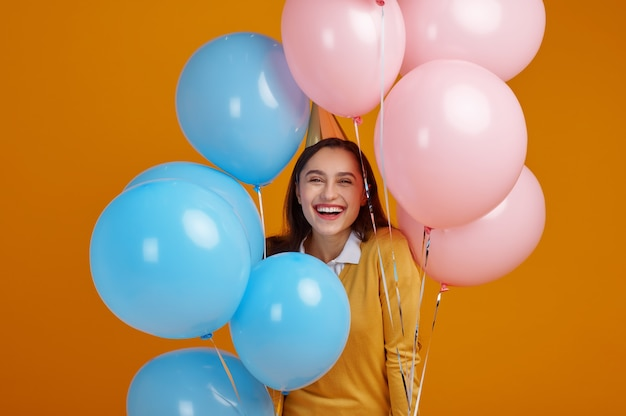 Funny woman in cap, yellow background. pretty female person got a surprise, event or birthday celebration, balloons