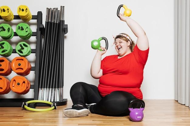 スポーツウェアに身を包んだ面白い女性は、他のスポーツ用品の隣のジムでダンベルを使って運動しています