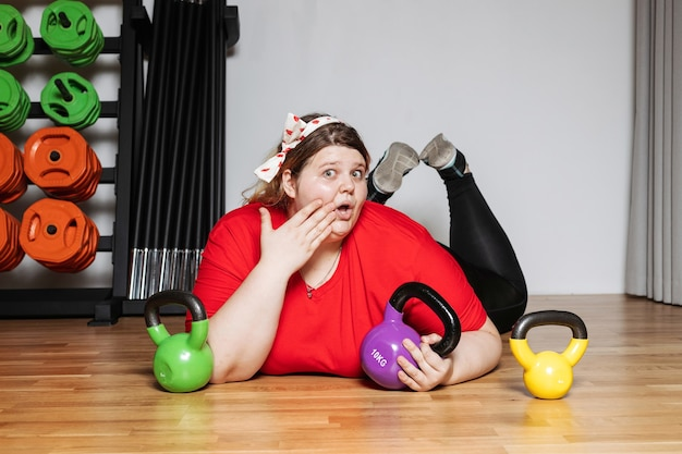 Funny woman dressed in the sports wear is laying on the floor next to the dumbbells in the gym with sports equipment