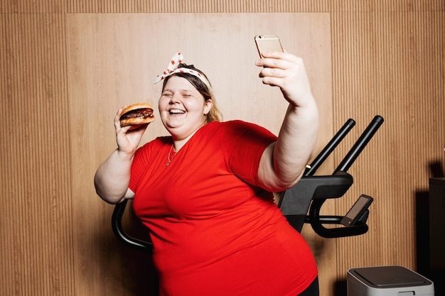 Funny woman dressed in sportswear and with a bandage on her head is making selfie standing with burger in her hand next to the treadmill