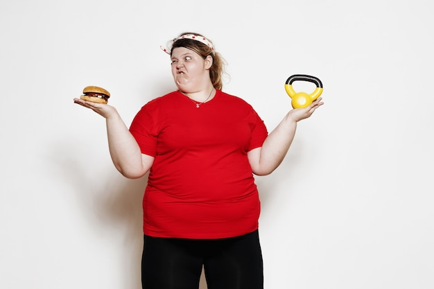 Funny woman dressed in sportswear and with a bandage on her head is standing with a burger in the one hand and the weight in the other against a white wall