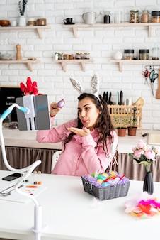 그녀의 친구를 온라인으로 인사하고, 부활절을 축하하고, 다채로운 계란으로 그녀의 눈을 가리는 재미 있은 여자