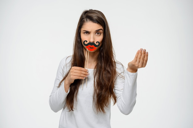 Funny woman grimacing in fake moustache and lips