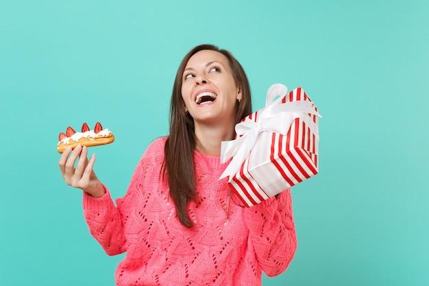 見上げるピンクのセーターの面白い女性、エクレアケーキ、青い背景で隔離のギフトリボンと赤い縞模様のプレゼントボックスを保持します。バレンタイン、女性の日、誕生日の休日のコンセプト。コピースペースをモックアップします。
