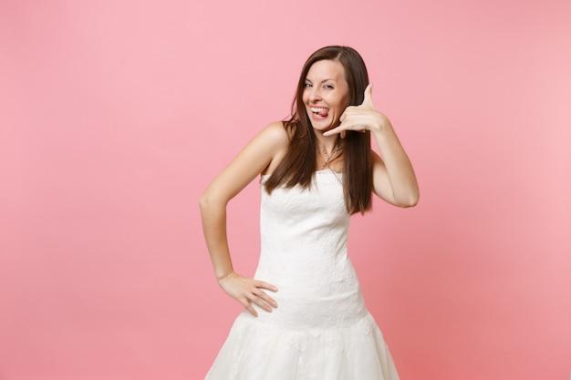 하얀 드레스를 입고 웃긴 여자가 같은 전화 제스처를하고 말합니다 : 전화로 이야기하는 것처럼 손과 손가락으로 다시 전화하십시오.