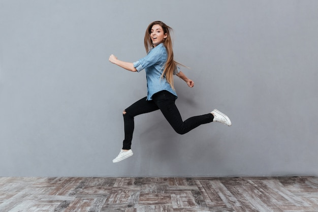 Funny woman jumping in studio