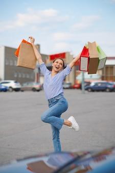 Смешная женщина прыгает с картонными мешками на автостоянке супермаркета. счастливые клиенты, несущие покупки из торгового центра, автомобили на заднем плане