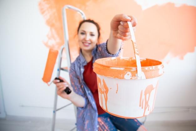 新しい家の壁を描いている面白い女性。改修、修理、改装のコンセプト。