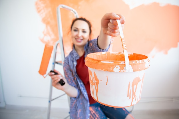 Funny woman painting the walls of new home. renovation, repair and redecoration concept.
