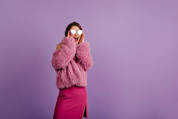 보라색 벽에 감정적으로 포즈를 취하는 재미있는 여자