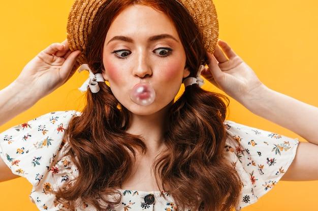 Смешная женщина надевает канотье и смотрит на пузырь жевательной резинки. портрет молодой женщины с двумя хвостиками.