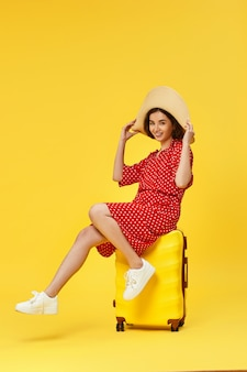 Funny woman in red dress with suitcase going traveling on yellow background.