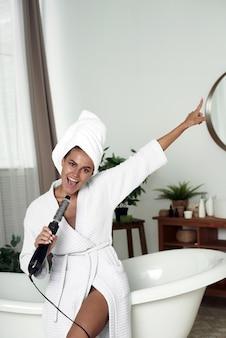 집에서 헤어 드라이어에서 노래하는 재미있는 여자.