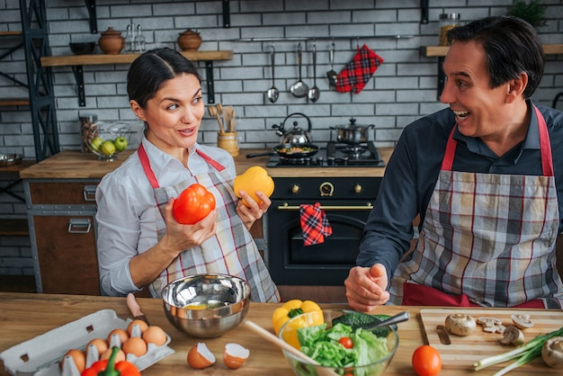 Funny woman sit in front of man in kitchen. she hold peppers on breast area and look at him. he laughing. they wear aprons.