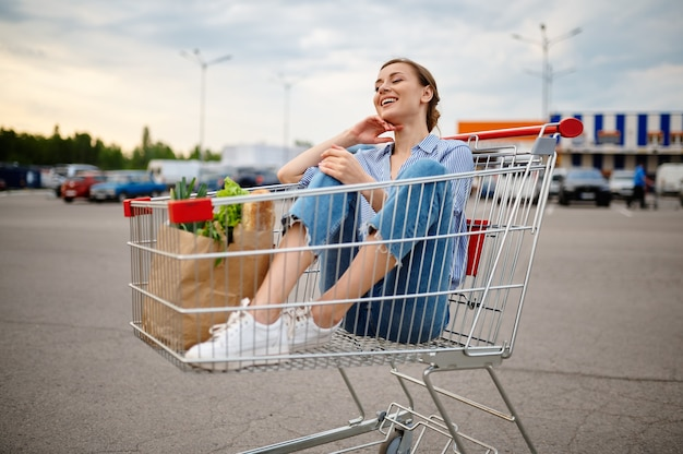 Funny woman sitting in cart on supermarket car parking. happy customer with purchases in shopping center, vehicles