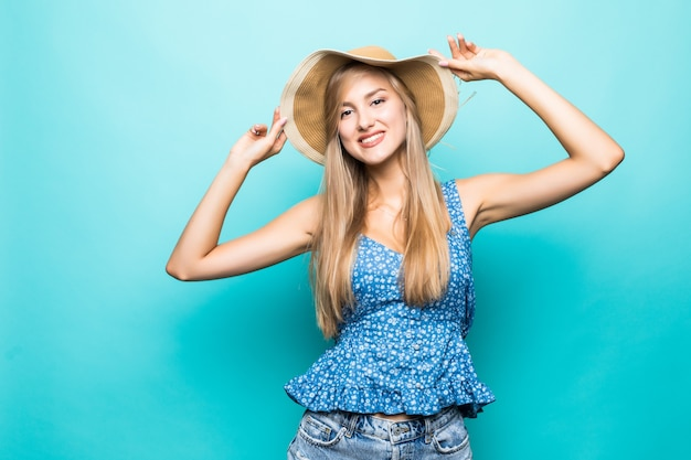 Funny woman in straw hat showing tongue standing near blue wall, fun, lifestyle, indoor