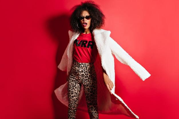 Donna divertente in occhiali da sole in posa sul muro rosso con la bocca aperta