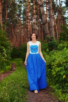 Funny woman walking in the forest. summer. the concept of lifestyle, nature and travel.
