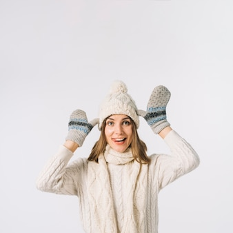 Funny woman in warm clothes grimacing for camera