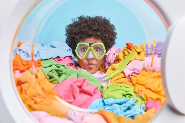 Funny woman with afro hair covered with multicolored laundry in washer makes fish lips wears snorkeling mask pretends to dive poses from inside of washing machine