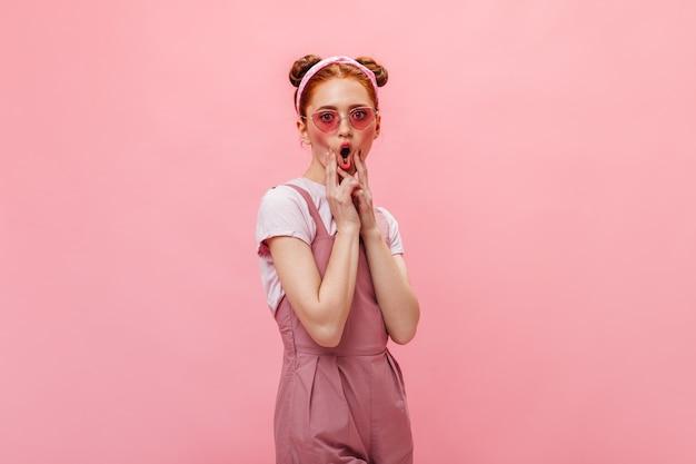 만두와 함께 재미있는 여자는 얼굴을 만든다. 분홍색 옷과 격리 된 배경에 포즈 안경에 여자.