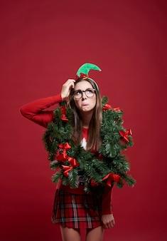 孤立したクリスマスの花輪を持つ面白い女性
